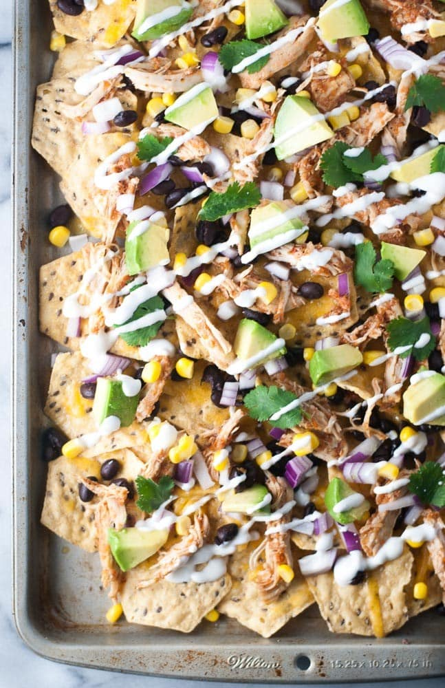 Overhead shot of shredded chicken nachos with avocado, red onion, corn, black beans, cilantro and drizzled with sour cream sauce