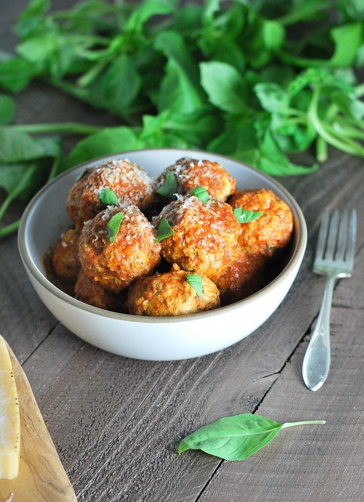 A bowl of turkey meatballs sprinkled with parmesan cheese and fresh basil with a fork laying next to the bowl