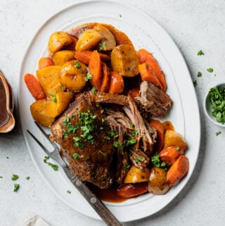 Cooked pot roast on a white platter with carrots and potatoes